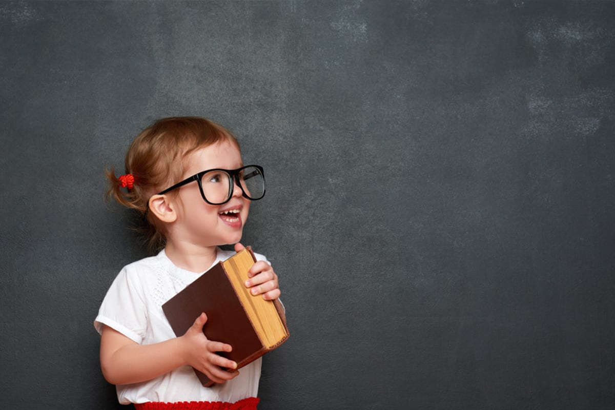 Little girl smiling while holding a book