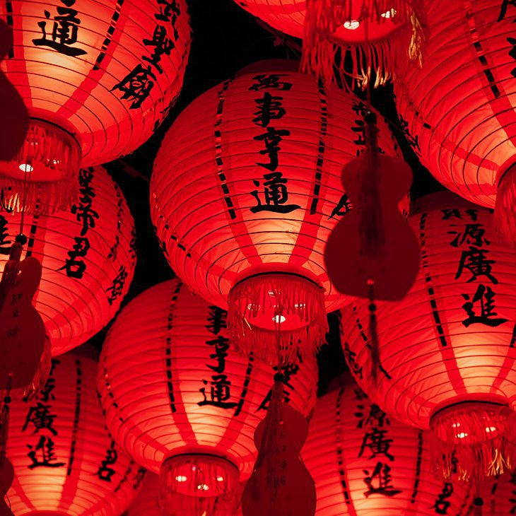 Red lanterns strung up on ceiling with chinese characters on the sides