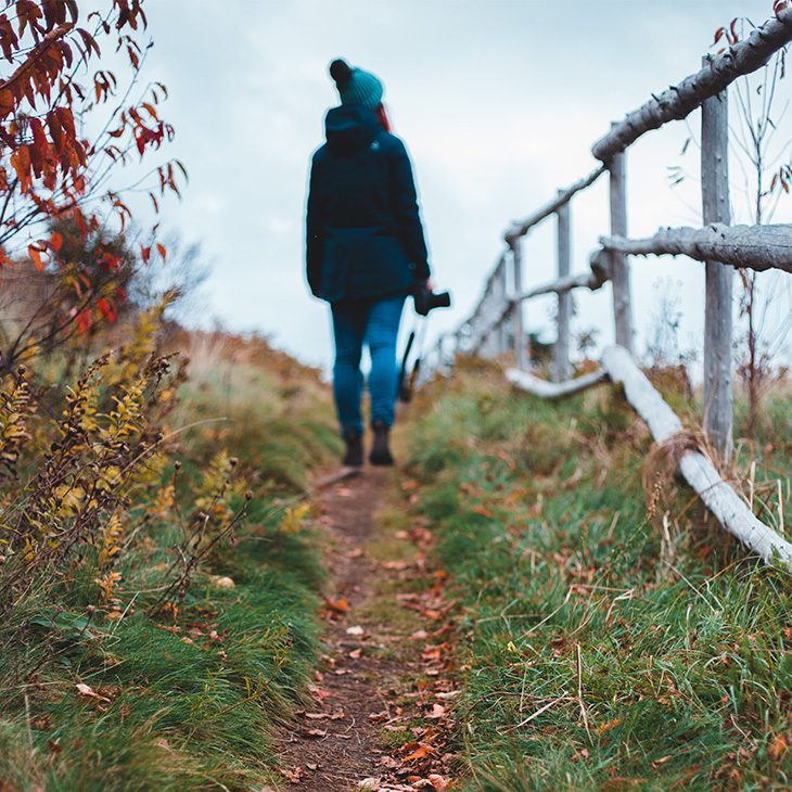Warmly dressed woman walking along dirt path next to white country fence with autumn leaves everywhere