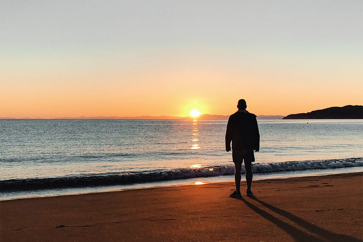Man staring at a sunrise at the beach