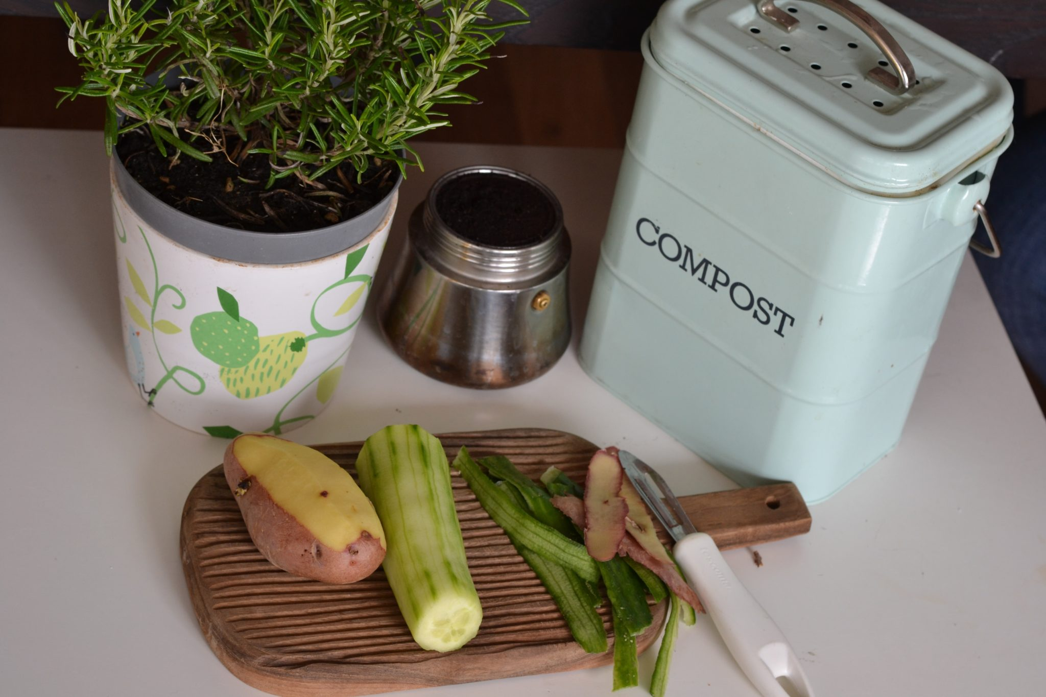 Chopping board with half peeled vegetables in front of a compost container