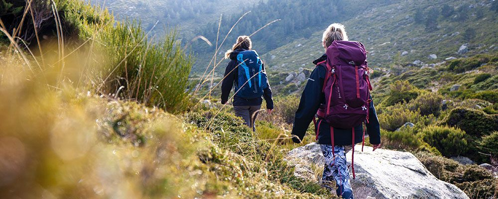 Two trekkers hiking single file in rocky, hilly country