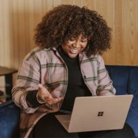 Smiling woman sitting on a couch with a laptop